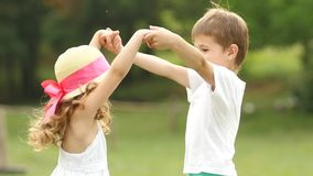As crianças guardam as mãos e começam-nas circundar junto no parque do verão Movimento lento vídeos de arquivo