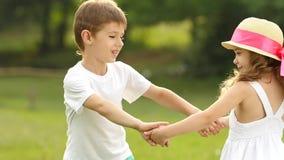 As crianças guardam as mãos e começam-nas circundar junto no parque do verão Movimento lento filme