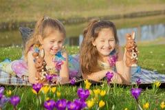 As crianças guardam coelhos pequenos coloridos do chocolate doce da Páscoa fotos de stock