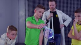 As crianças guardam a esfera de vidro acima da bobina de Tesla filme
