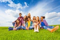 As crianças internacionais felizes sentam-se no prado verde Fotografia de Stock Royalty Free