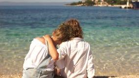 As crianças, irmã dos irmãos sentam-se na costa do mar de Adriad Paz e tranquilidade, crianças felizes, resto maravilhoso video estoque