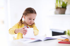 As crianças leem, escrevem e pintam Criança que faz trabalhos de casa Imagens de Stock Royalty Free