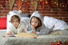 As crianças leram um grande livro com contos do Natal Imagem de Stock