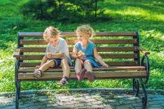 As crianças menino e menina que sentam-se em um banco pelo mar e comem uma maçã Imagens de Stock Royalty Free