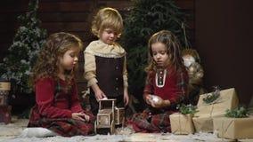 As crianças moldam bolas de neve e põem-nas em um carro do brinquedo entre os presentes do Natal e as decorações, movimento lento