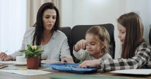 As crianças muito carismáticas duas meninas e um menino têm uma boa estadia com sua mãe madura na tabela elas pintura video estoque