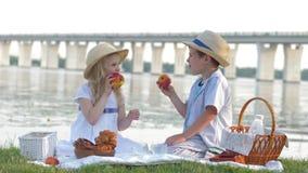 As crianças na natureza, no rapaz pequeno bonito com fome e na menina em chapéus de palha comem maçãs no piquenique na natureza a vídeos de arquivo