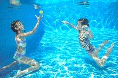 As crianças nadam na associação subaquática, meninas ativas felizes têm o divertimento sob a água Imagem de Stock