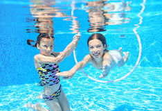 As crianças nadam na associação subaquática, meninas ativas felizes têm o divertimento sob a água Fotos de Stock
