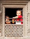 As crianças nepalesas olham da janela em Bhaktapur, Nepal. Fotografia de Stock Royalty Free