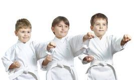 As crianças no karategi estão batendo o perfurador do karaté imagens de stock