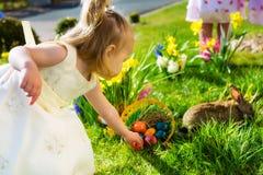 As crianças no ovo da páscoa caçam com coelho Imagens de Stock Royalty Free