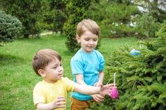 As crianças no ovo da páscoa caçam no jardim de florescência da mola Crianças que procuram por ovos coloridos no prado da flor Me foto de stock royalty free