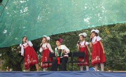 As crianças no terno nacional cantam na cena no dia da cidade Fotos de Stock Royalty Free