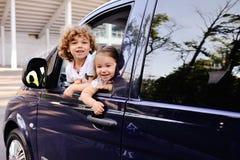 As crianças olham para fora de uma janela de carro Fotografia de Stock