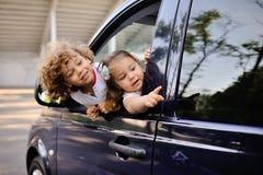 As crianças olham para fora de uma janela de carro Fotos de Stock