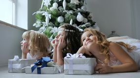 As crianças olham sonhadoramente o inverno fora da janela com as caixas de presente no assoalho no fundo da árvore de Natal decor video estoque