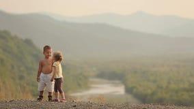 As crianças pequenas bonitas alegres estão guardando as mãos e estão beijando-as no fundo da paisagem bonita durante vídeos de arquivo