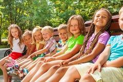 As crianças pequenas bonitas sentam-se no banco no parque Fotografia de Stock