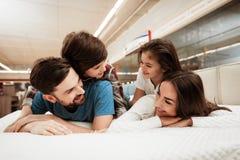 As crianças pequenas encontram-se nas partes traseiras de pais felizes novos em uma loja do colchão Fotografia de Stock Royalty Free