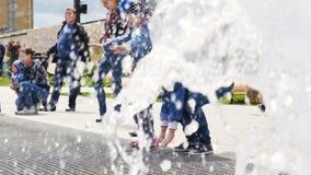 As crianças pequenas exultam o jogo perto da fonte no parque do entretenimento vídeos de arquivo