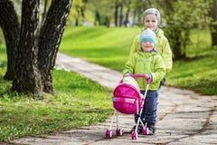 As crianças pequenas, o irmão e a irmã jogam na jarda com um transporte de bebê do brinquedo Crianças que jogam no parque verde n Imagens de Stock Royalty Free