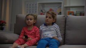 As crianças pequenas que olham a televisão surpreendida pela porta aberta, pais controlam vídeos de arquivo