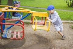 As crianças pequenas rolam-se em balanços dos carrosséis no campo de jogos do ` s das crianças na jarda o menino e uma menina mon fotos de stock royalty free