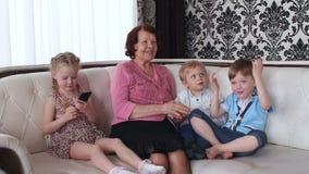 As crianças pequenas sentam-se com a avó no sofá vídeos de arquivo
