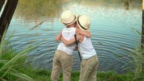 As crianças pescam no banco de uma lagoa As crianças estão na costa do lago com hastes filme