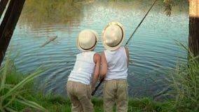 As crianças pescam no banco de uma lagoa As crianças pescam no banco de uma lagoa As crianças estão na costa do lago com vídeos de arquivo