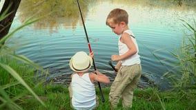 As crianças pescam no banco de uma lagoa Duas crianças pequenas travam peixes em uma lagoa na dacha filme
