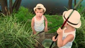 As crianças pescam no banco de uma lagoa O lago bonito no dia de verão vídeos de arquivo