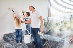 As crianças pintam a parede na renovação da casa fotos de stock royalty free