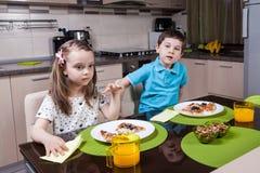 As crianças prées-escolar comem a pizza na cozinha fotografia de stock