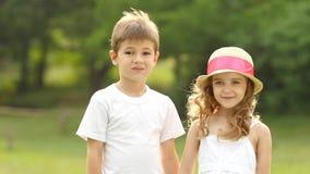 As crianças que andam no parque estão guardando as mãos e estão olhando na distância Movimento lento vídeos de arquivo
