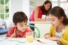 As crianças que fazem trabalhos de casa como a mãe usam o portátil Fotos de Stock