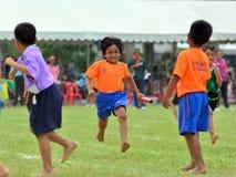 As crianças que fazem uns trabalhos de equipa correm a competência no dia do esporte do jardim de infância Fotos de Stock