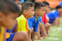 As crianças que fazem uns trabalhos de equipa correm a competência no dia do esporte do jardim de infância Fotografia de Stock