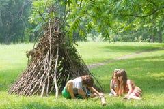As crianças que jogam ao lado da vara de madeira abrigam a vista como a cabana indiana, fotografia de stock royalty free