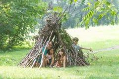 As crianças que jogam ao lado da vara de madeira abrigam a vista como a cabana indiana, imagem de stock