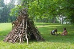As crianças que jogam ao lado da vara de madeira abrigam a vista como a cabana indiana, imagem de stock royalty free