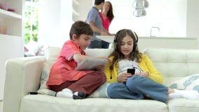 As crianças que jogam com dispositivos de Digitas como pais fazem a refeição vídeos de arquivo