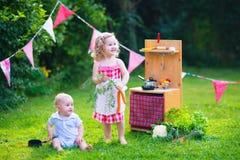 As crianças que jogam com uma cozinha do brinquedo em um verão jardinam Fotos de Stock