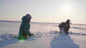 As crianças que jogam no inverno no ar fresco, lance aumentam rapidamente Esportes exteriores ativos vídeos de arquivo