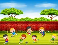 As crianças que jogam o futebol com sua equipe junto na jarda ilustração stock