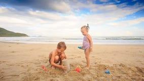 As crianças que louras o menino pequeno da menina cabriola fazem o bolo de areia na praia filme