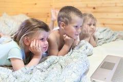 As crianças que olham o computador monitoram ao colocar na cama fotografia de stock
