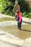 As crianças que saltam e que espirram em poças enlameadas Imagem de Stock Royalty Free